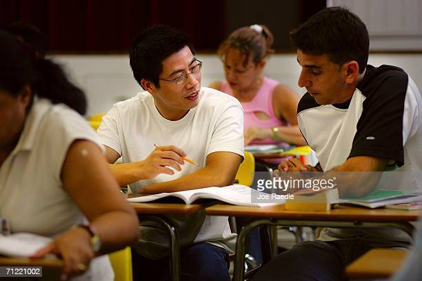Heng Lin originally from China and Jose Bolano orginally from Cuba learn how to speak English in class at the English Center June 16 2006 in Miami...
