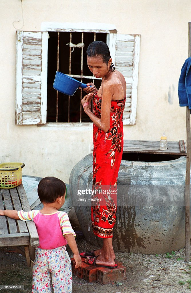 Heng Phala, 24, talks with her son, David, 2, as she takes her evening bath from a cistern outside their apartment. She has been HIV+ for about two years and nearly died of the disease. A recent drug regimen has made her much healthier and prepared her to begin taking ARV drugs. Phala lives with her mother Phaly, 65, and her son David, 2, in a one-room apartment on the outskirts of the Cambodian capital. Her illness has left her too weak to work and she and her mother have a difficult time paying their bills. Phala believes she was infected with HIV by her husband, who has left her..