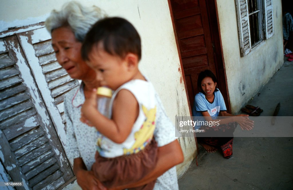 Heng Phaly, 65, holds her two-year-old grandson David as her daughter Phala, 24, sits in their doorway. All three share a one-room apartment on the outskirts of Phnom Penh. For about the last two years, Phala has been HIV+. She was very sick and nearly died before she began a recent medical regimen to prepare her to take ARV drugs. Phala believes she was infected by her husband, who has left her..