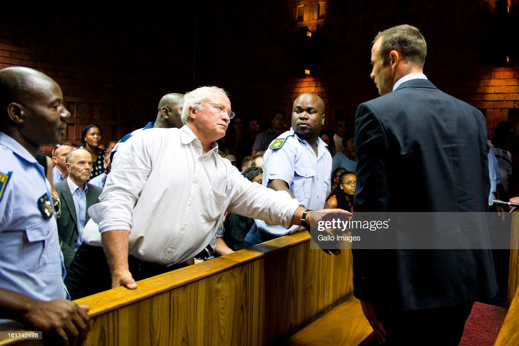 Henke Pistorius reaches out to son Oscar Pistorius during the Pretoria Magistrate court hearing on February 15, 2013, in Pretoria, South Africa. Oscar Pistorius stands accused of murder after shooting girlfriend Reeva Steenkamp on the morning of February 14, 2013. His bail hearing has been postponed until February 19, 2013, with prosecutors stating they will pursue a charge of premeditated murder against him.