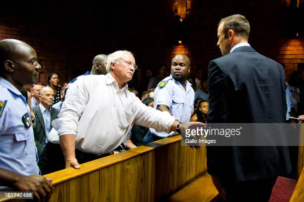 Henke Pistorius reaches out to son Oscar Pistorius during the Pretoria Magistrate court hearing on February 15 in Pretoria, South Africa. Oscar...