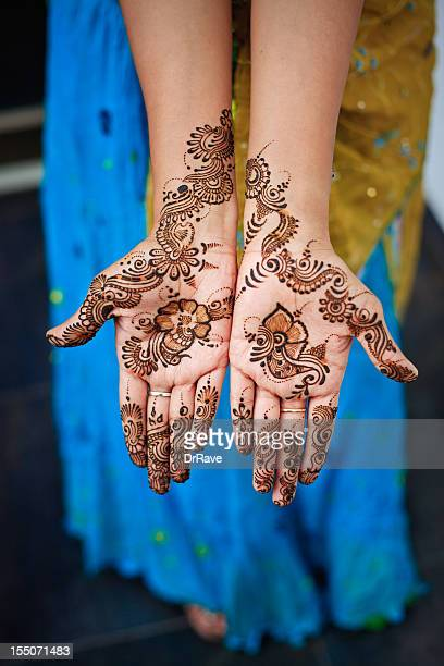 Henna on both hands of Indian woman wearing sari