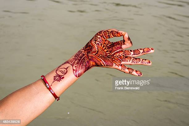 RISHIKESH UTTARAKHAND INDIA A henna painted hand is showing the mudra 'Gyan Mudra' at the ghats of the holy river Ganges