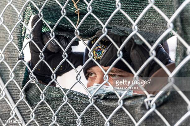 Hennepin County sheriff looks through a security fence outside the Hennepin County Government Center on March 9, 2021 in Minneapolis, Minnesota. -...
