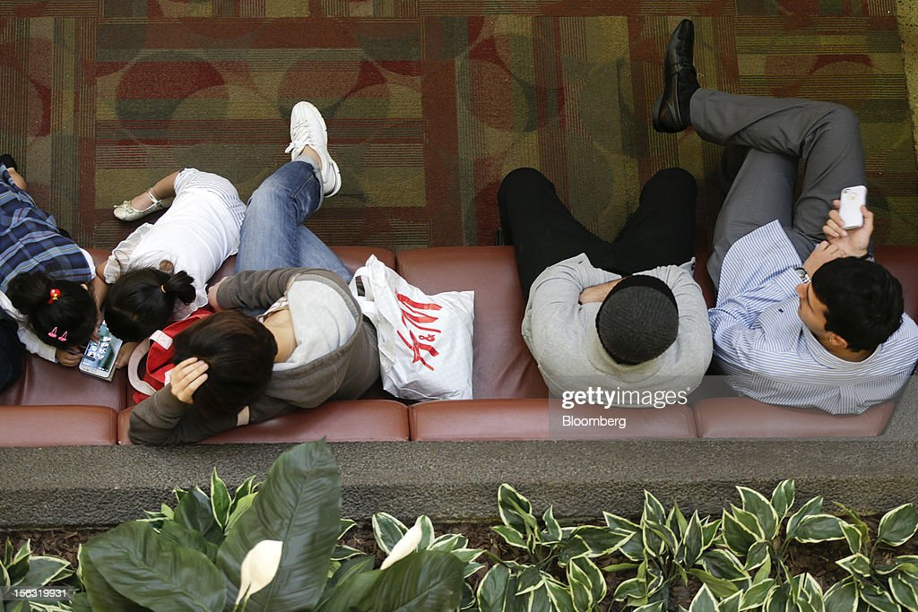 A Hennes & Mauritz AB (H&M) bag sits next to shoppers taking a break at the Fair Oaks Mall in Fairfax, Virginia, U.S., on Monday, Nov. 12. 2012. Sales at U.S. retailers probably fell in October for the first time in four months economists said before a report on Nov. 14. Photographer: Andrew Harrer/Bloomberg via Getty Images