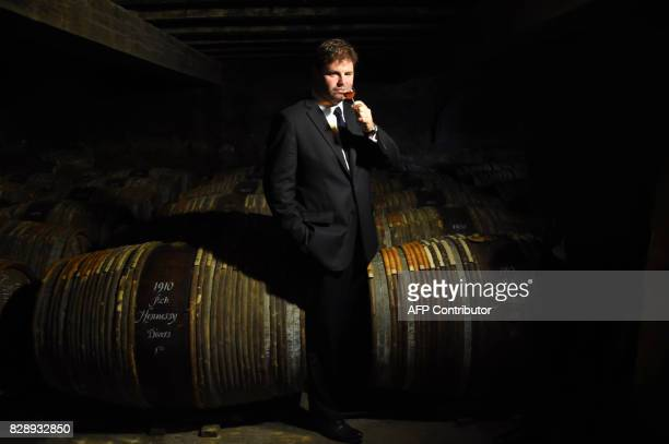 Hennessy's 8th generation Master Blender Renaud Fillioux poes with a glass of cognac on August 2 2017 in the cellars at the cognac estate of Hennessy...