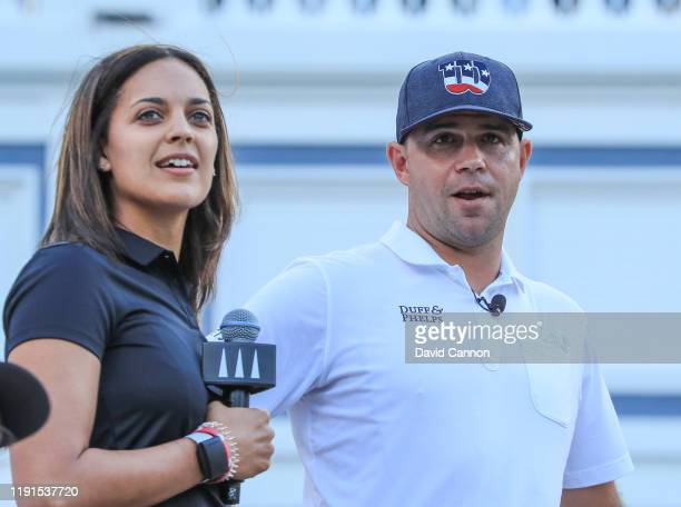 Henni Zuel the Golf Channel television presenter watches a shot with Gary Woodland of the United States on stage during the 'Hero Shot at Baha Mar'...