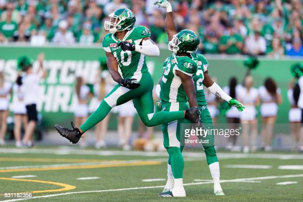 Henoc Muamba and Tobi Antigha of the Saskatchewan Roughriders celebrate after a quarterback sack in the first half of the game between the BC Lions...