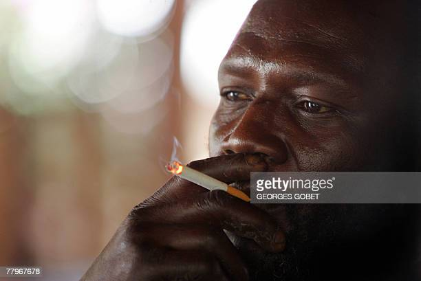 Henri a fisherman waiting for another attempt to immigrate to Europe after twice being returned from Spain smokes a cigarette 08 November 2007 in a...