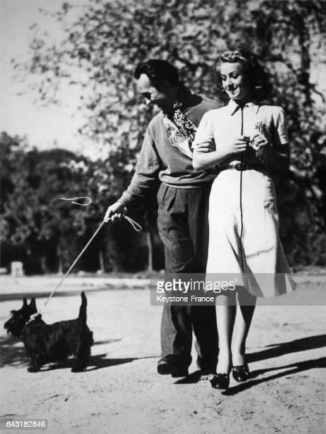 Henri Decoin et sa femme Danielle Darrieux se promenant avec leur chien à Hollywood Los Angeles aux EtatsUnis le 4 mars 1938