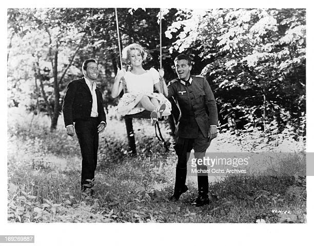 Henri Garcin and Carlos Thompson pushing Catherine Deneuve on a swing in a scene from the film 'A Matter Of Resistance' 1966