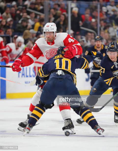Henri Jokiharju of the Buffalo Sabres checks Darren Helm of the Detroit Red Wings as he goes for the puck during the first period at KeyBank Center...