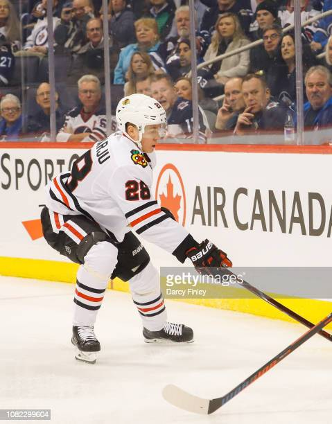 Henri Jokiharju of the Chicago Blackhawks plays the puck behind the net during first period action against the Winnipeg Jets at the Bell MTS Place on...