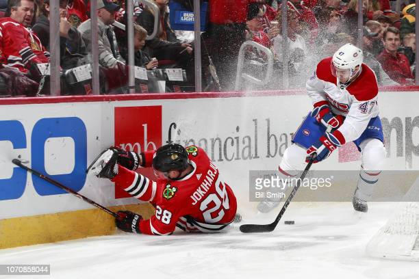 Henri Jokiharju of the Chicago Blackhawks slides into the boards ahead of Kenny Agostino of the Montreal Canadiens in the first period at the United...