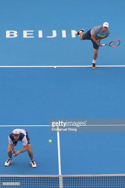 Henri Kontinen of Finland and John Peers of Australia serve during their Men's double semi finals match against Paolo Lorenzi of Italy and Mischa...