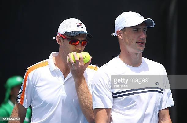 Henri Kontinen of Finland and John Peers of Australia talk tactics during their first round doubles match against Santiago Gonzalez of Mexico and...