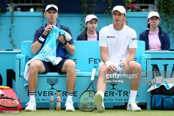 Henri Kontinen of Finland and playing partner John Peers of Australia look on as they take a seat during a change of ends during their Quarter-Final...