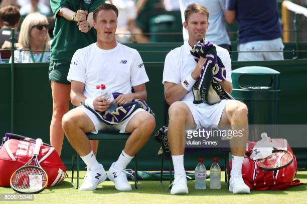 Henri Kontinen of Finland speaks to his partner John Peers of Australia during a break between sets during the Gentlemen's Doubles first round match...