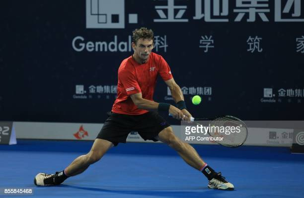 Henri Laaksonen of Switzerland hits a return against David Goffin of Belgium during their men's singles semifinal match at the ATP Shenzhen Open...