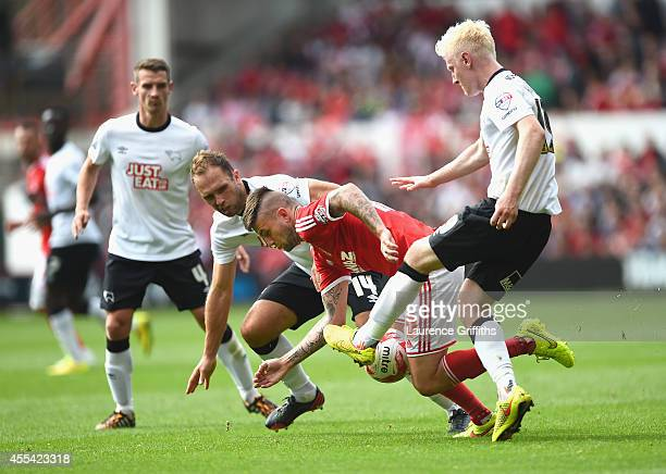 Henri Lansbury of Nottingham Forest battles for the ball with John Eustace and Will Hughes of Derby County during the Sky Bet Championship match...