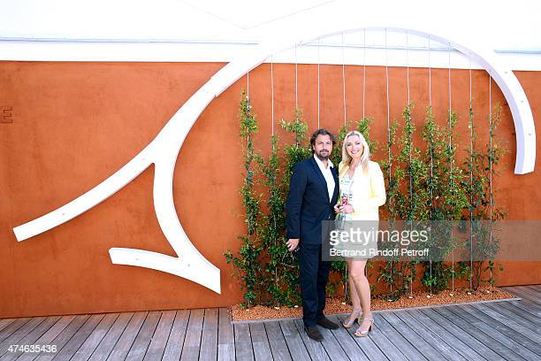 Henri Leconte and a Village hostess attend the 2015 Roland Garros French Tennis Open at Roland Garros on May 24 2015 in Paris France