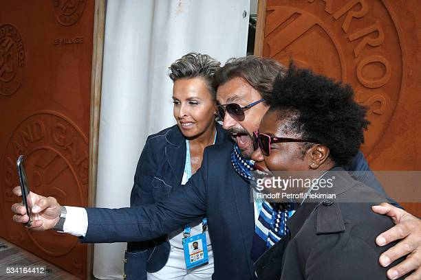 Henri Leconte standing between Humorist Claudia Tagbo and Maria attend the 2016 French Tennis Open Day Four at Roland Garros on May 25 2016 in Paris...