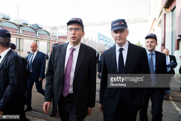 Henri PoupartLafarge chief executive officer of Alstom SA left and Bruno Le Maire France's finance minister walk between factory buildings during a...