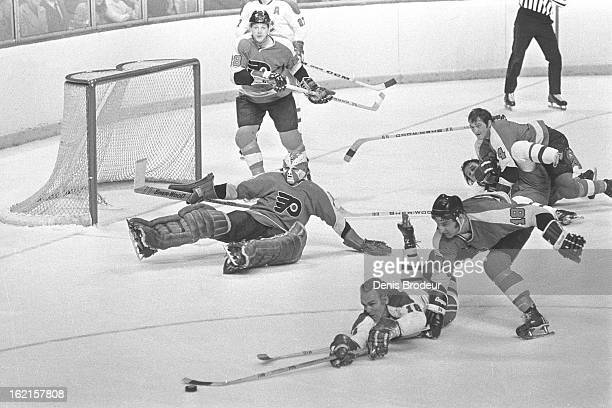Henri Richard of the Montreal Canadiens dives for the puck against Ross Lonsberry of the Philadelphia Flyers while goalie Doug Favell of the Flyers...
