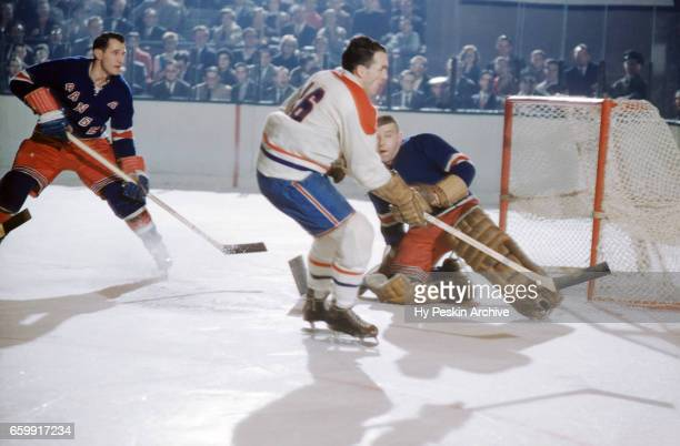 Henri Richard of the Montreal Canadiens goes for the puck as goalie Lorne Gump Worsley and defenseman Harry Howell of the New York Rangers defend the...