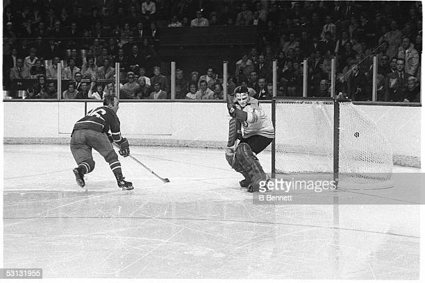 Henri Richard of the Montreal Canadiens scores against goalie Ed Johnston of the Boston Bruins circa 1960's at the Montreal Forum in Montreal Quebec...