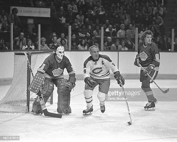 Henri Richard of the Montreal Canadiens skates between goalie Gary Edwards and Sheldon Kannegiesser of the Los Angeles Kings during a game at the...