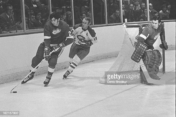 Henri Richard of the Montreal Canadiens skates for the puck against Serge Lajeunesse of the Detroit Red Wings while goalie Joe Daley of the Redwings...