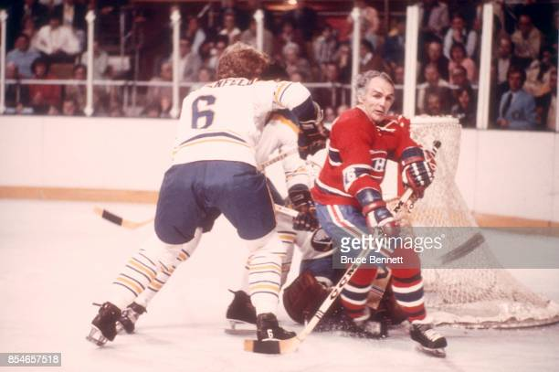 Henri Richard of the Montreal Canadiens skates on the ice as he is defended by Jim Schoenfeld of the Buffalo Sabres circa 1973 at the Buffalo...