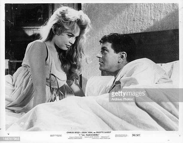 Henri Vidal and Brigitte Bardot in bed together looking at on an other with affection in a scene from the film 'La Parisienne' 1957