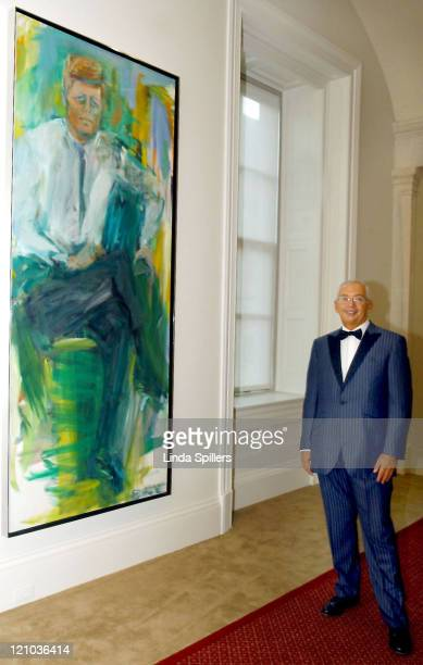 Henri Zimand founder of Zimand Entertainment in front of a portrait of President John F Kennedy