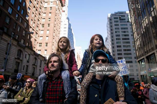 Henrietta Hamilton and Marlowe Sturridge ride on their fathers' shoulders as they march on Sixth Avenue during the March For Our Lives March 24 2018...