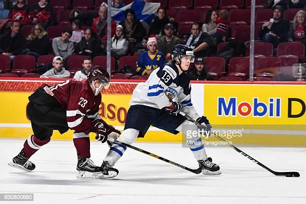 Henrik Borgstrom of Team Finland skates the puck against Karlis Cukste of Team Latvia during the 2017 IIHF World Junior Championship relegation game...