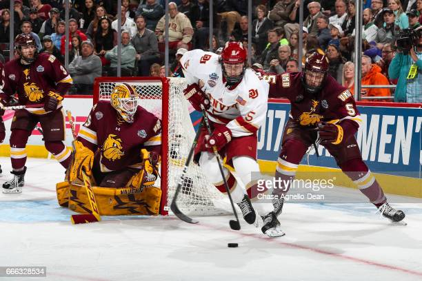 Henrik Borgstrom of the Denver Pioneers and Nick Wolff of the MinnesotaDuluth Bulldogs chase the puck in the third period during the 2017 NCAA Div I...
