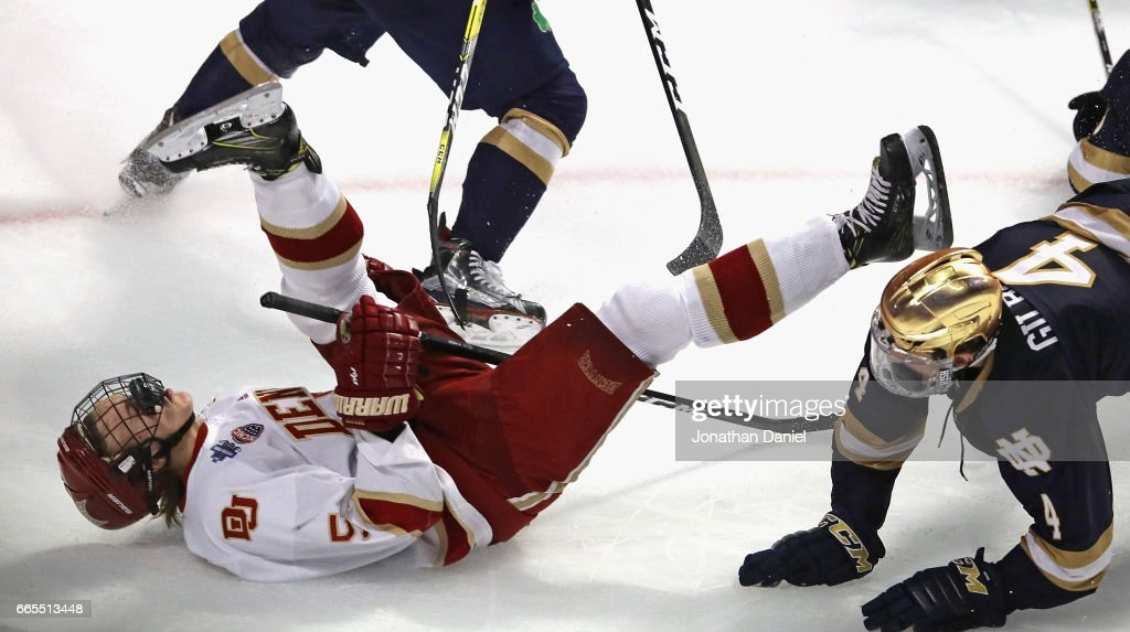 Henrik Borgstrom #5 of the Denver Pioneers is knocked to the ice by Dennis Gilbert #4 of the Notre Dame Fighting Irish during game two of the 2017 NCAA Division I Men's Hockey Championship Semifinal at the United Center on April 6, 2017 in Chicago, Illinois. Denver defeated Notre Dame 6-1.