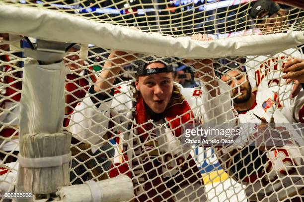 Henrik Borgstrom of the Denver Pioneers looks through the net after cutting a piece while celebrating winning the 2017 NCAA Div I Men's Ice Hockey...
