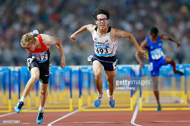 Henrik hannemann of Germany and Gyeongtae Kim of Korea competes in the Men's 110m Hurdles Final of Nanjing 2014 Summer Youth Olympic Games at the...