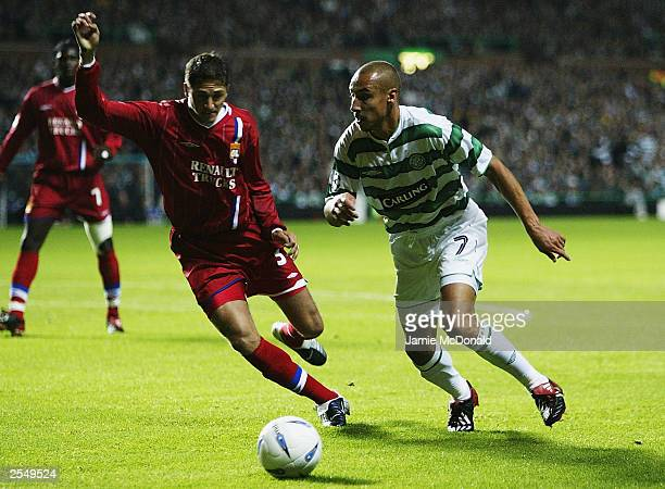 Henrik Larsson of Celtic gets past Edmilson of Lyon during the UEFA Champions League Group A match between Glasgow Celtic and Olympique Lyonnais at...