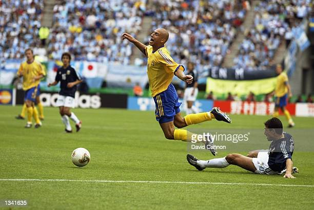 Henrik Larsson of Sweden is brought down by Kily Gonzalez of Argentina during the Group F match of the World Cup Group Stage played at the Miyagi...