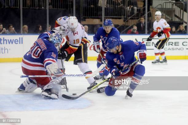 Henrik Lundqvist and Steven Kampfer of the New York Rangers defend the goal against the Calgary Flames during their game at Madison Square Garden on...
