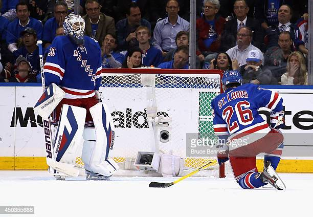 Henrik Lundqvist of the New York Rangers and Martin St Louis of the New York Rangers react to a goal by Jake Muzzin of the Los Angeles Kings during...
