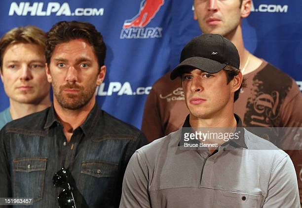Henrik Lundqvist of the New York Rangers and Sidney Crosby of the Pittsburgh Penguins listen to the NHLPA press conference at Marriott Marquis Times...