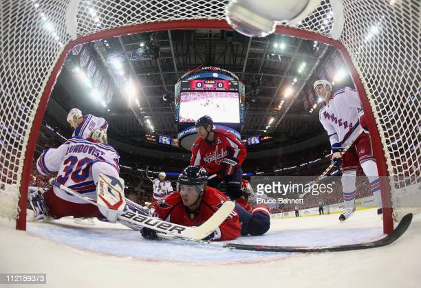 Henrik Lundqvist of the New York Rangers blocks the net as Marcus Johansson of the Washington Capitals slides into him in Game One of the Eastern...