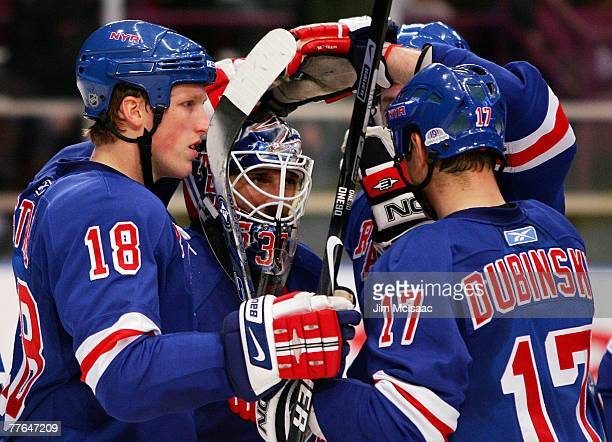 Henrik Lundqvist of the New York Rangers celebrates his shutout victory against the Washington Capitals with teammates Marc Staal and Brandon...