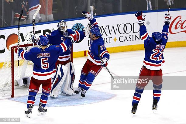 Henrik Lundqvist of the New York Rangers celebrates with teammate Dan Girardi Ryan McDonagh and Brian Boyle after defeating the Montreal Canadiens in...