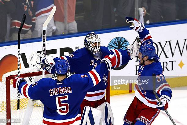 Henrik Lundqvist of the New York Rangers celebrates with teammate Dan Girardi and Ryan McDonagh after defeating the Montreal Canadiens in Game Six to...